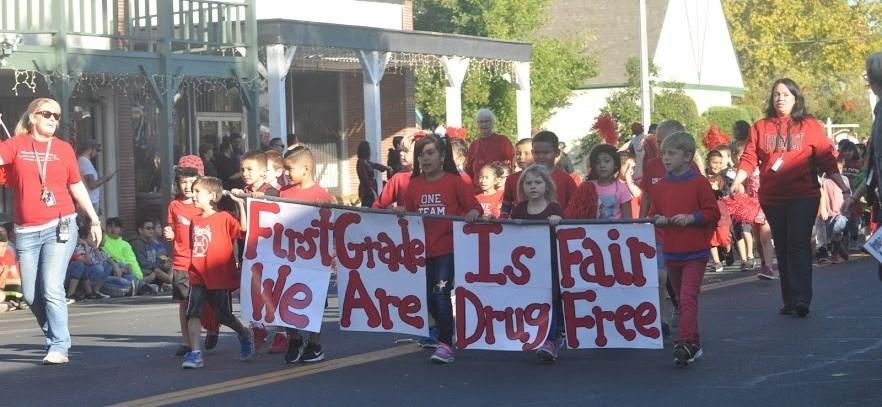 Students walking with banner at Red Ribbon Parade