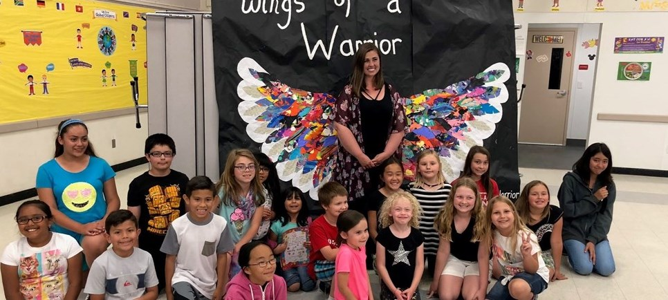 Students at art show posing with giant wings